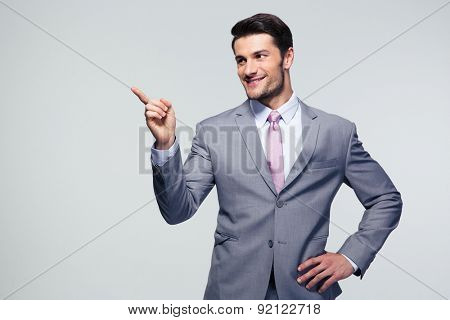 Handsome smiling businessman pointing finger away over gray background