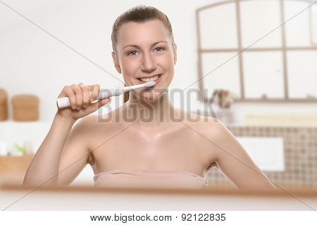 Smiling Woman Using An Electric Toothbrush