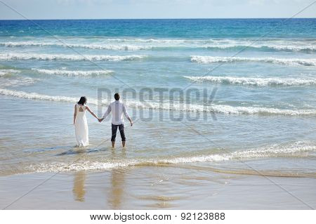 Bride And Groom Walking On The Beach In Sunny Day