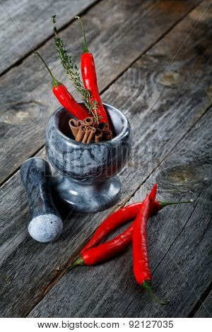 Mortar With Cinnamon And Chilli Pepper On An Old Table