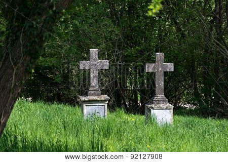 Two Old  Stone Crosses As Tombstones In An Overgrown Cemetery