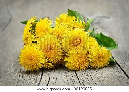 Dandelion Flowers On Wooden Background