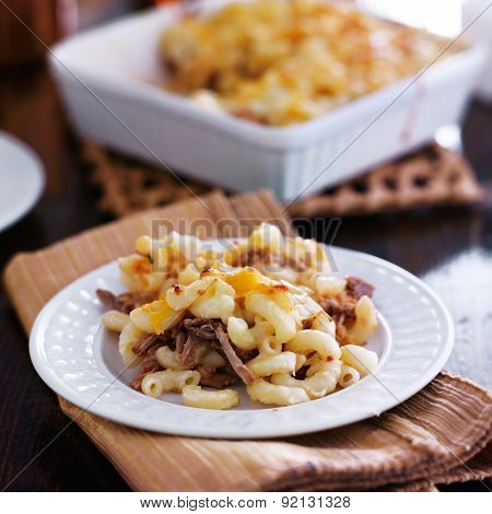 plate of baked macaroni and cheese casserole with barbecue pulled pork