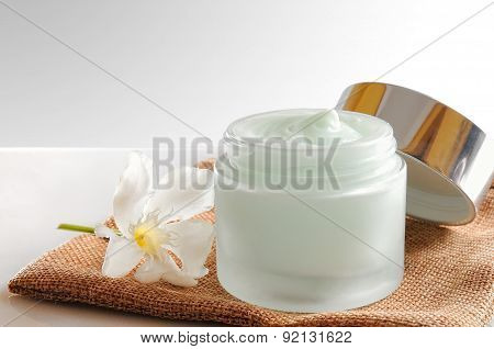 Glass Open Jar With Cream On Burlap White Isolated