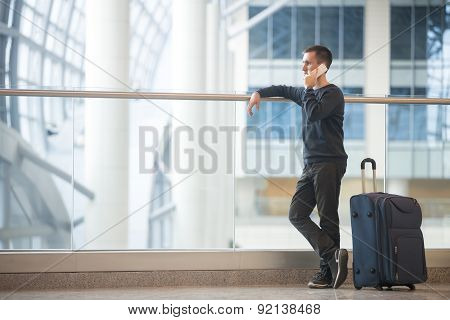 Young Traveler Talking On Smartphone In Airport