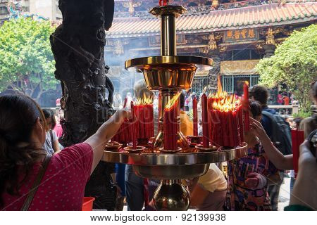 Taiwanese women lighting candles at Longshan Temple