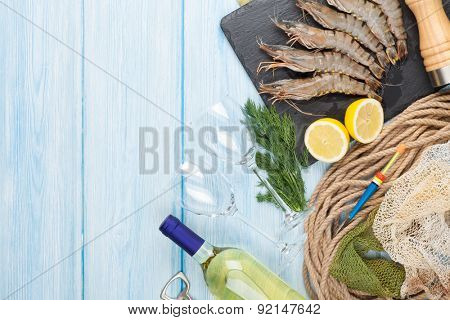 Fresh raw tiger prawns, spices and white wine on wooden table with copy space