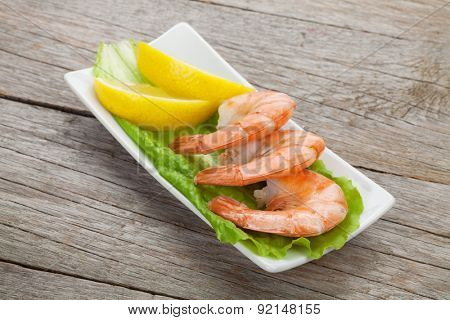 Cooked shrimps with lemon and salad leaves. On wooden table