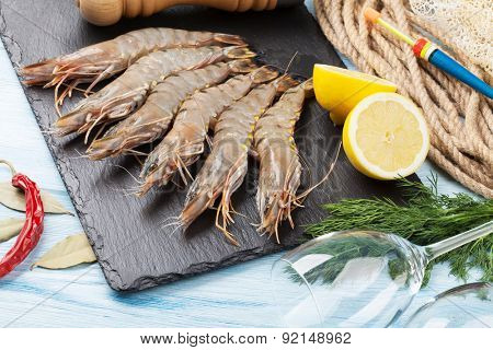 Fresh raw tiger prawns and fishing equipment on wooden table
