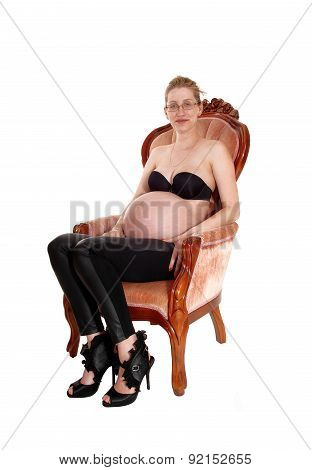 Pregnant White Woman In Armchair.