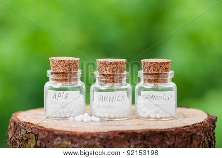 Bottles With Homeopathy Globules On Green Background
