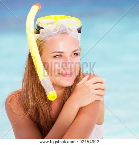 Portrait of beautiful blond girl wearing cute yellow  snorkeling mask, sitting on the beach shore, active lifestyle, enjoying water sport, summer holidays and vacation