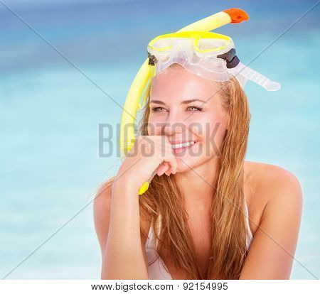 Portrait of beautiful blond girl wearing cute yellow diving mask sitting on the beach, active lifestyle, enjoying water sport, summer vacation concept