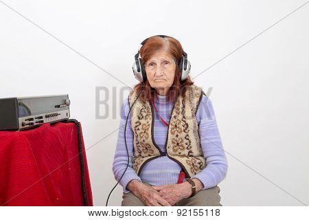 Elderly Lady Listening To The Radio.