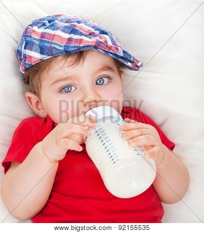 Portrait of cute little hungry baby boy drinking milk, lying on the bed and eating, baby food formula, healthy nutrition for kids