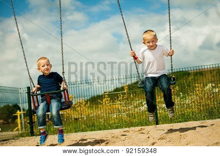 Little Boys Brothers Having Fun On A Swing Outdoor