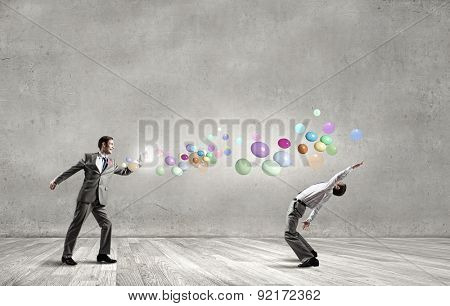 Young businessman trying to evade from thrown colorful balloons