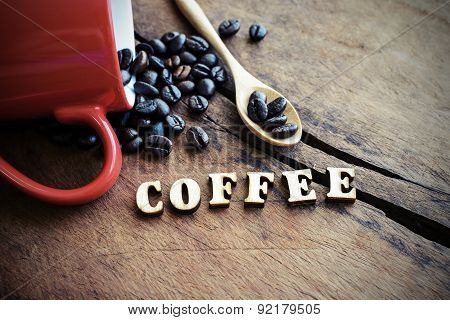 Red Cup Of Coffee With Wooden Spoon And Coffee Bean On Old Wooden Textured
