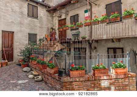 Courtyard in front of house with pots and flowers in small town of Barolo in Piedmont, Northern Italy.