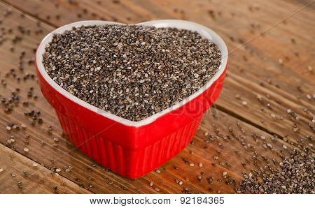 Chia Seeds In A Heart Shaped Bowl On  Rustic Wooden Table.