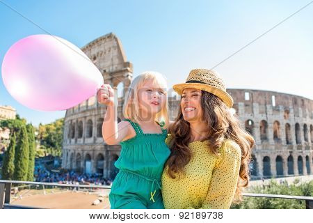 Smiling Mother And Daughter With Pink Balloon By Colosseum