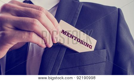 Businessman Holds Wooden Piece With Mentoring Text
