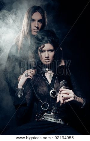 Romantic portrait of young gothic couple - man and woman over dark background.