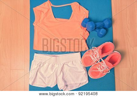 Workout clothes - fitness outfit and running shoes. Overhead of clothing ready for lifting weights at the gym or at home, laying on a yoga mat on the floor. Matching orange t-shirt and sneakers.