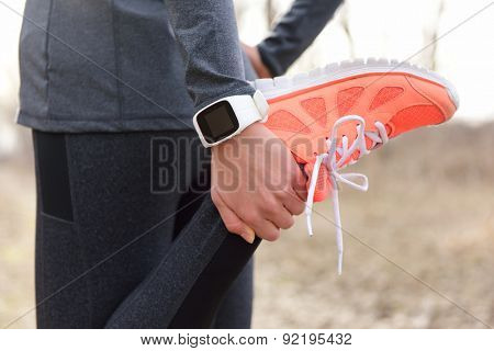 Running stretching - runner wearing smartwatch. Closeup of running shoes, woman stretching leg as warm-up before run with sport activity tracker watch at wrist to monitor the heart rate during cardio.