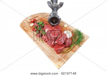 uncooked fresh beef meat chunks on wooden cutting plate with green hot and red peppers and grinder isolated over white background