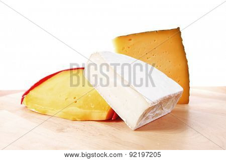 group of french aged delicatessen cheeses on wooden table