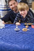 stock photo of dreidel  - Boy with father and grandfather spinning dreidel focus on dreidel - JPG
