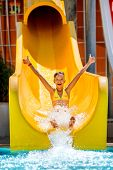 stock photo of inflatable slide  - Child on water slide at aquapark - JPG