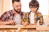 stock photo of protective eyewear  - Concentrated young male carpenter teaching his son to work with wood in his workshop - JPG