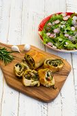 picture of rocket salad  - Dough rolls strudel with swiss chard and chorizo on chopping board young garlic with lettuce and rocket leaves salad chopped radishes white painted wood background - JPG