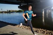 stock photo of leggins  - Young handsome man running along the embankment near the river under the bridge