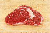 stock photo of rib eye steak  - Raw rib eye steak on a wooden board - JPG