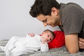 picture of cuddle  - Loving father cuddling his new born baby - JPG