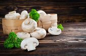 stock photo of champignons  - Champignons with parsley in a basket on a wooden table - JPG