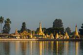 stock photo of shimmer  - Golden stupas shimmer in Pone Taloke Lake Pindaya Myanmar in the morning sun - JPG