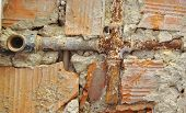 picture of levers  - Broken water pipes in a broken brick wall - JPG