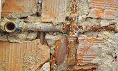 foto of hot water  - Broken water pipes in a broken brick wall - JPG