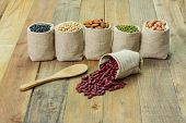 pic of kidney beans  - Different kinds of beans in sacks bag focus on scattered kidney beans - JPG