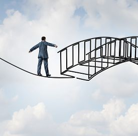 picture of risk  - Risk reduction concept as a businessman on a tightrope walking on a wire that becomes shaped as a safe three dimensional bridge as a symbol of security and controlling uncertainty with a protection guarantee increase - JPG