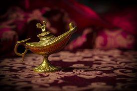 foto of aladdin  - Macro image of a tiny gold antique Aladdin lamp ornament close - JPG