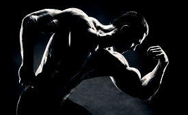 image of bicep  - bodybuilder demonstrates biceps on a dark background is over contrast - JPG