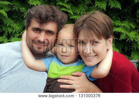 Little happy boy hugging mom and dad