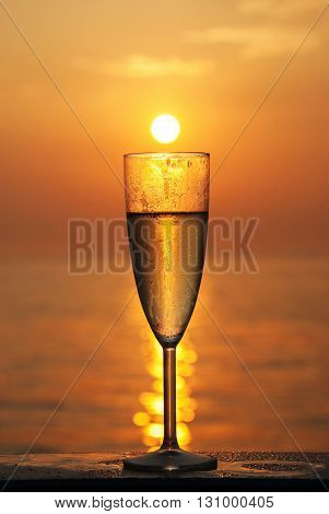 A glass of wine on the background of the rising sun