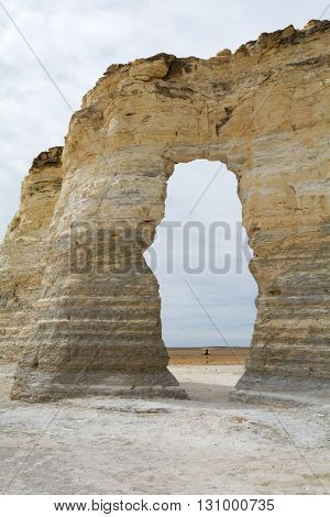 A flat brown prairie is visible behind a natural limestone arch.