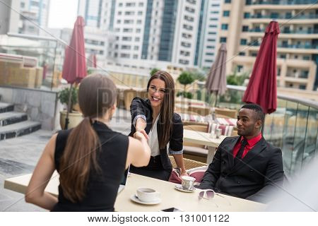 Two young businesswoman handshaking and negotating business.